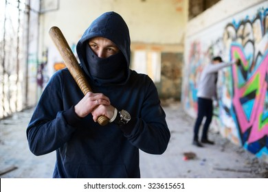 unrecognizable vandal with wooden baseball bat.