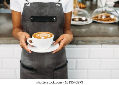 Unrecognizable waitress holding a cup of latte with rosetta in cafe