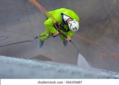 unrecognizable window cleaner works on high rise building.Window cleaning is considered one of the most dangerous job in the world.Several window cleaners die each year and many are injured