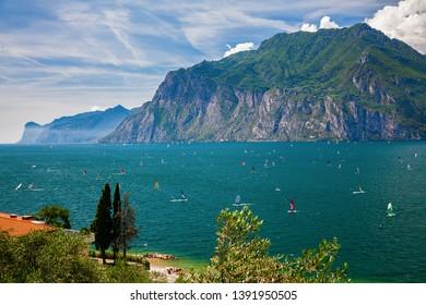 unrecognizable windsurfers surfing on a Garda lake near Torbole and Riva del Garda, Italy