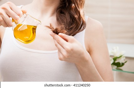 Unrecognizable woman applying oil mask to hair tips in a bathroom; beauty and haircare concept