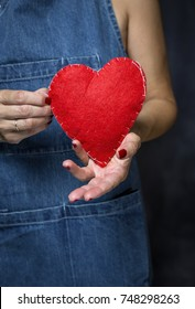 Unrecognizable woman with blue apron and valentines day heart in hand
