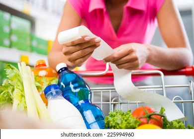 Unrecognizable woman checking a long grocery receipt leaning to a full shopping cart at store.