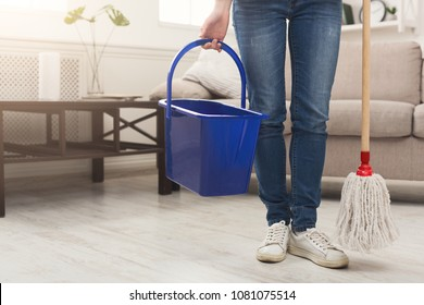 Unrecognizable woman with cleaning equipment ready to clean house. Cropped girl holding mop, professional cleaning service concept, copy space