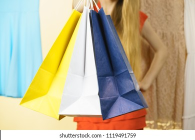 Unrecognizable woman in clothes shop store holding shopping bags picking summer perfect outfit, dress hanging on clothing hangers