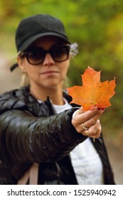 unrecognizable woman in dark hiking jacket, white shirt and black cap holding orange maple leaf in the beginning of autumn in canada., very blurred background, small depth of field