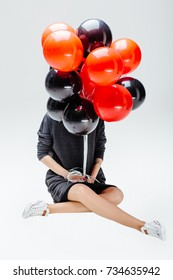 Unrecognizable woman in dress and sneakers covering her face a lot of red and black balloons before face. Sale, holiday and celebration concept.