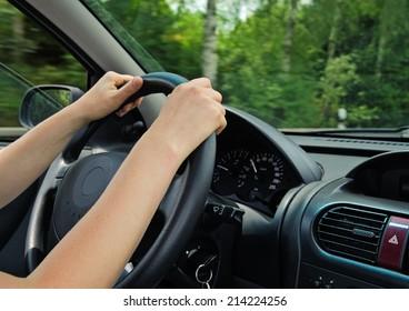 An unrecognizable woman driving a car