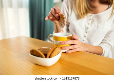 Unrecognizable woman eating cookies and milk for breakfast