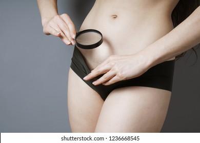 虫眼鏡をかけて性器の領域を調べている、見分けがつかない女性 – 女性の性、性病、または女性の健康に関するコンセプト