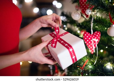 Unrecognizable woman in front of Christmas tree with present