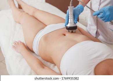Unrecognizable woman getting full body rf-lifting procedure by cosmetician at the salon