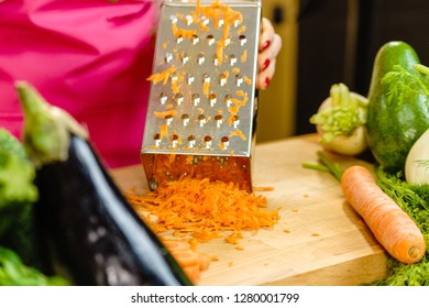 Unrecognizable woman grating carrot on metal grater, kitchen utensil making food preparing healthy vegetable salad. - Shutterstock ID 1280001799