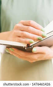Unrecognizable woman in green dress and with beautiful manicure reading a book, front  view.