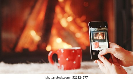 Unrecognizable Woman Hands Taking Cozy Picture on the SmartPhone by the Burning Fireplace - Close Up. Girl making photos of comforting fireside and festive cup scene on a phone