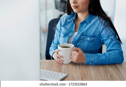 Unrecognizable woman at her desk with a cup of coffee