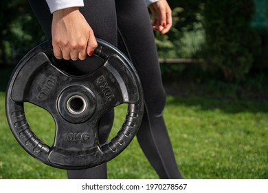 An unrecognizable woman holding a 10 kg barbell disc with handles and working out in the park