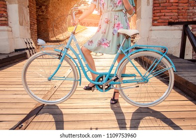 Unrecognizable woman holding blue retro bicycle in sunset on wooden bridge