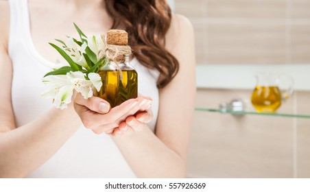 Unrecognizable woman holding bottle of natural olive oil and beautiful fresh flowers; concept of gentle organic haircare and skincare