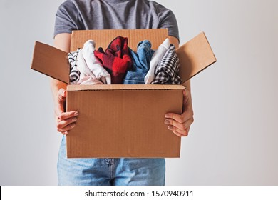 Unrecognizable woman holding box with clothes in it. close-up. Clothing donation.