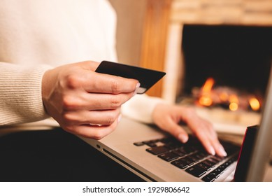 Unrecognizable woman holding credit card and using laptop computer while online shopping. Businesswoman working from home. Internet banking, money transfers concept.