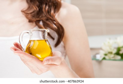 Unrecognizable woman holding glass jug with virgin olive oil - skincare and haircare concept