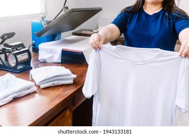 unrecognizable woman, holding white shirts behind a sublimation or screen printing machine for t-shirts. graphic design concept.