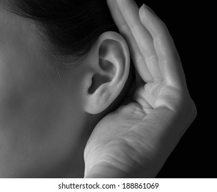 Unrecognizable woman holds her hand near ear and listens, close-up