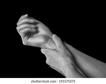 Unrecognizable woman holds her hand, pain in the wrist, black and white image