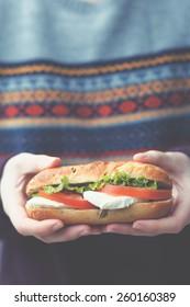 Unrecognizable woman holds sandwich