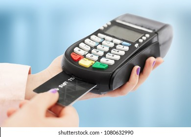 Unrecognizable woman holds swiping machine and credit card, pays for purchase, uses bank terminal in shop, isolated over blue background. POS terminal in store.