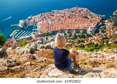 unrecognizable woman looking at the Dubrovnik Old Town, sitting on the mountain above the city, Croatia