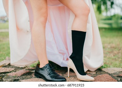 d3d4a2ccb12 Unrecognizable woman naked legs in men sock black leather footwear. Unknown  bride in expensive wedding
