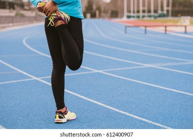 An unrecognizable woman on a stadium warming up before workout. Horizontal outdoors shot.