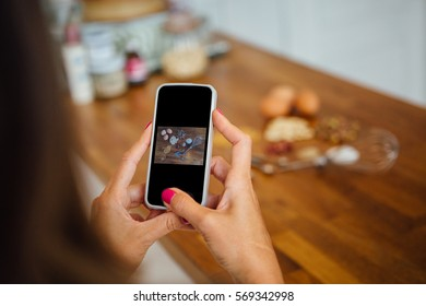 Unrecognizable woman with phone taking photo of uncooked ingredients on table.Unfocused background