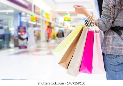 Unrecognizable woman with purchases in shopping mall, blurred background, copy space