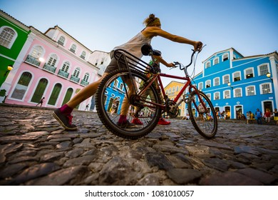 Unrecognizable woman pushing a bike passes in front of colorful colonial architecture on a broad cobblestone hill in the historic city center of Pelourinho.