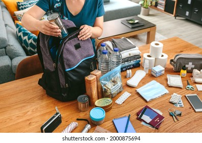 Unrecognizable woman putting cans of food to prepare emergency backpack in living room