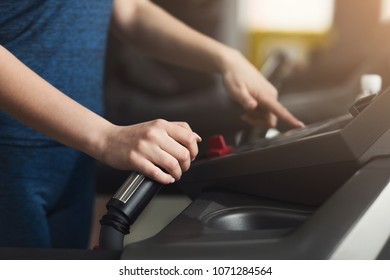 Unrecognizable woman running on treadmill in gym. Slim girl jogging in fitness club, turning elliptical trainer, closeup. Healthy lifestyle concept, cardio training, copy space