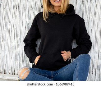 Unrecognizable woman sits in front of camera, she wears black hoodie. There is a place on hoodie for inscription or design for fashion mockup. Casual outfit for lady.  Sweatshirt template.