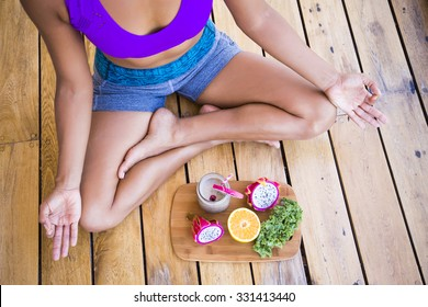 Unrecognizable woman sitting in lotus with fruits in front of her