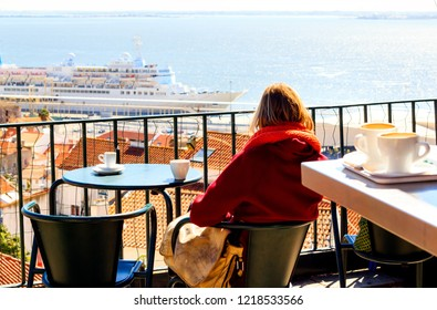 Unrecognizable woman is sitting in the open cafe overlooking Alfama district and sea in the center of Lisbon at Portas Do Sol neigbourhood, Portugal