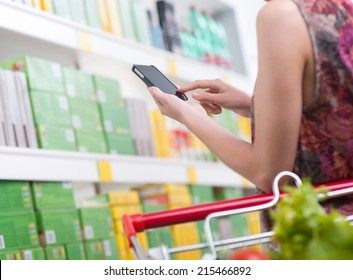 Unrecognizable woman at store using smartphone with shelves on background.