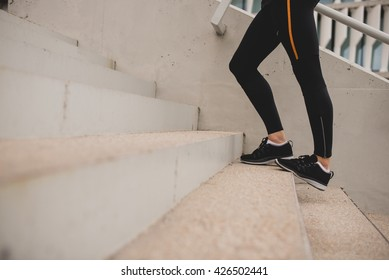 Unrecognizable woman stretching calves on steps