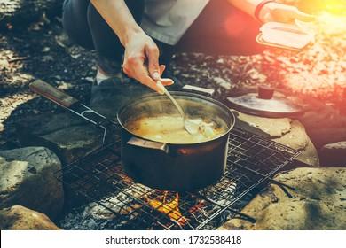 Une femme touriste méconnue qui cuisine au feu de camp dans la forêt. Concept Tourisme Camping Survie Wildlife