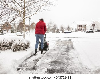 An unrecognizable woman uses a snowblower to clear snow from a driveway during a snow storm
