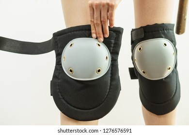 Unrecognizable woman wearing and adjusting her safety knee protectors pads. Safe workwear during construction work.