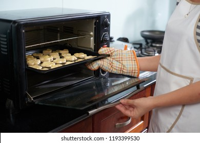 Unrecognizable woman wearing oven mitt putting baking sheet with raw cookies into modern oven in home kitchen