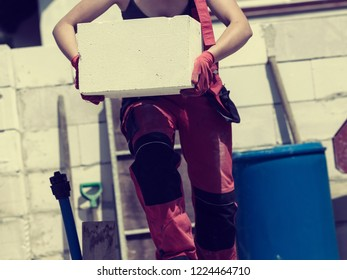 Unrecognizable woman working on construction site, building house, installing gray airbricks. Industrial work concept.