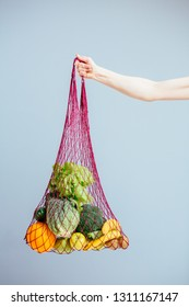Unrecognizable woman's hand holding a bag of mixed fruit, vegetables, greens. Zero waste concept. Vertical shot. Grey background. Healthy, mindfulness food, eating nutritional concept.